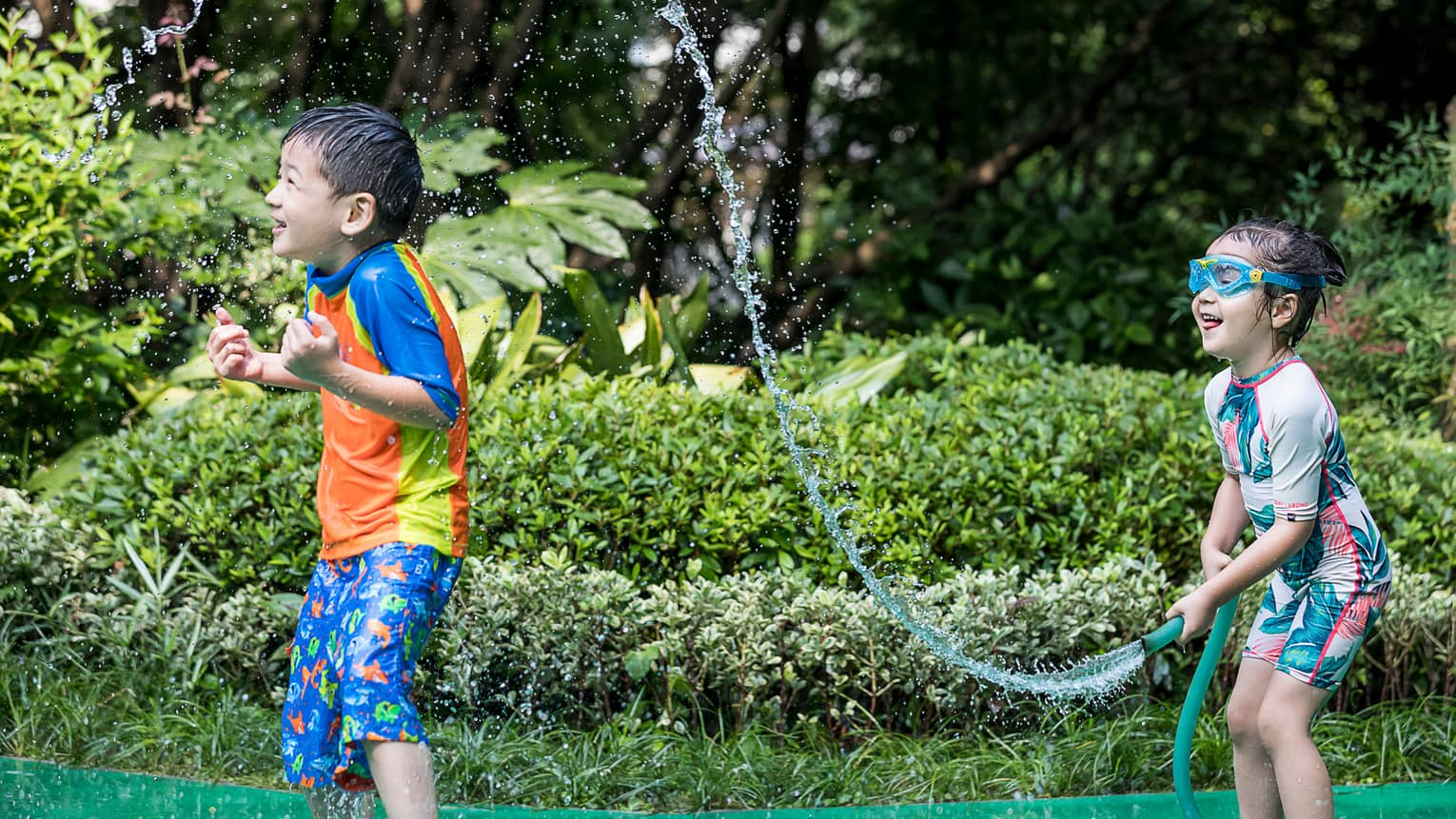 Young girl wearing swimsuit, goggles sprays boy with garden hose
