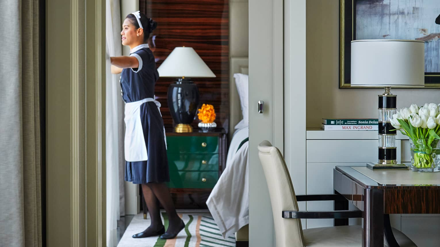 Housekeeper in black-and-white uniform draws curtains in hotel room on sunny day