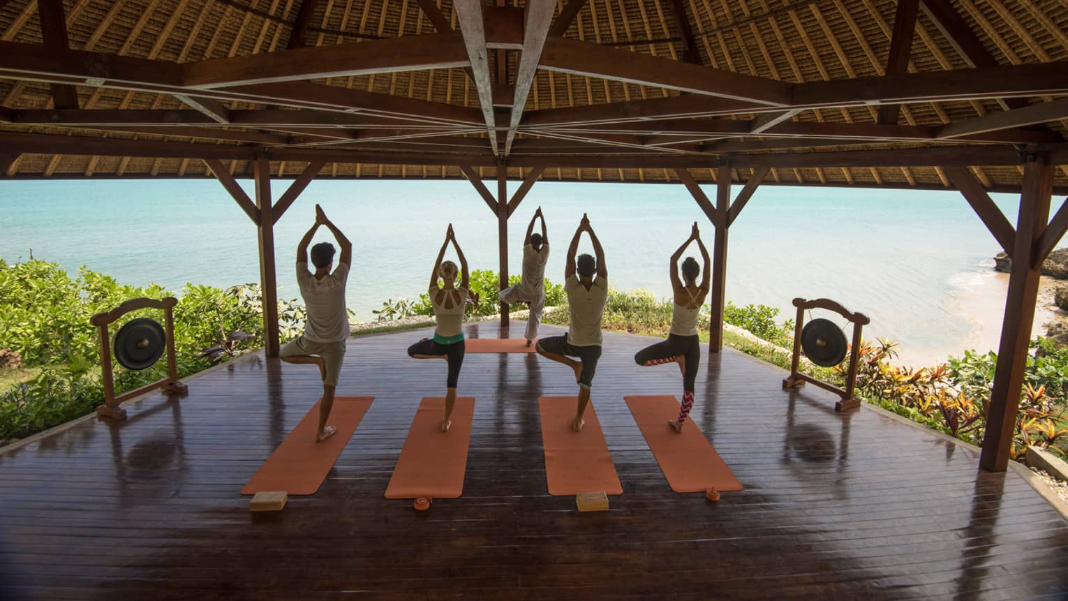 Four people stand in yoga poses, on mats in front of instructor under wood gazebo near ocean