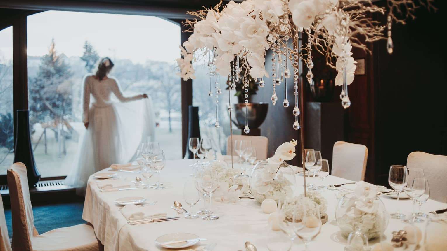 Bride holds train staring out window behind table with white orchids and glass icicles