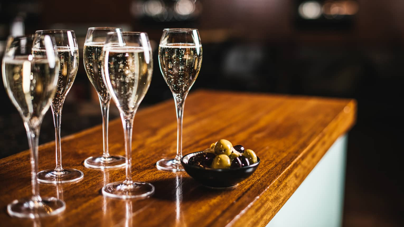 Five glasses of sparkling wine with bowl of black and green olives, atop a wooden bar top