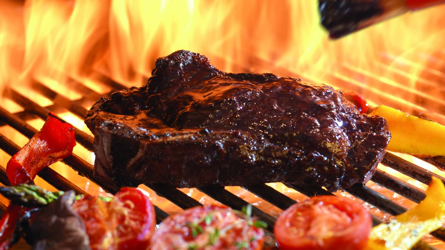 Close-up of juicy steak, tomato and pepper halves on barbecue grill with flames