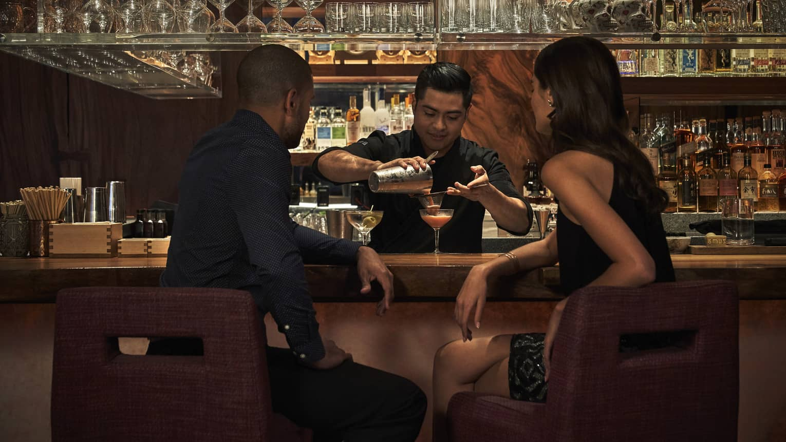Man and woman sit a bar and watch bartender pour their martinis