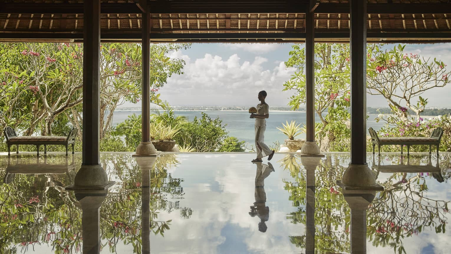 Hotel staff carrying flowers reflected onto floor of open-air pavilion