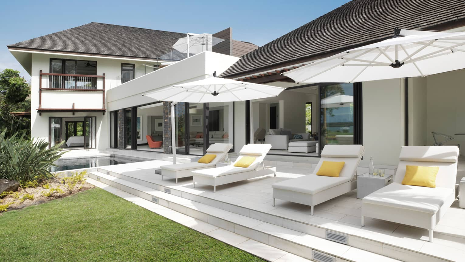 White lounge chairs under umbrellas on patio in front of large white two-storey villa