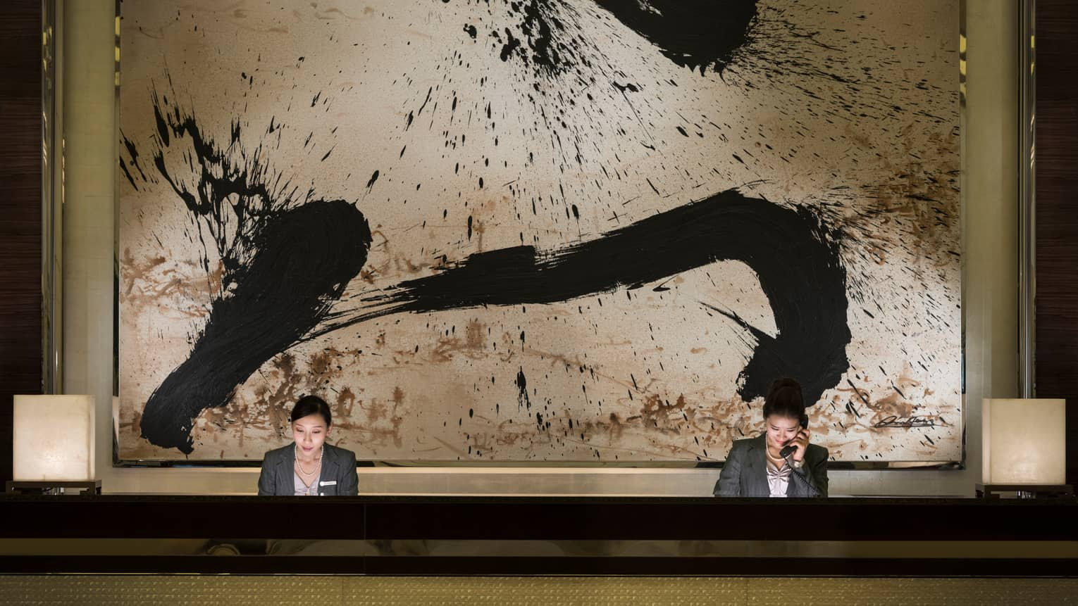 Two hotel reception staff at long desk under large black-and-white abstract painting