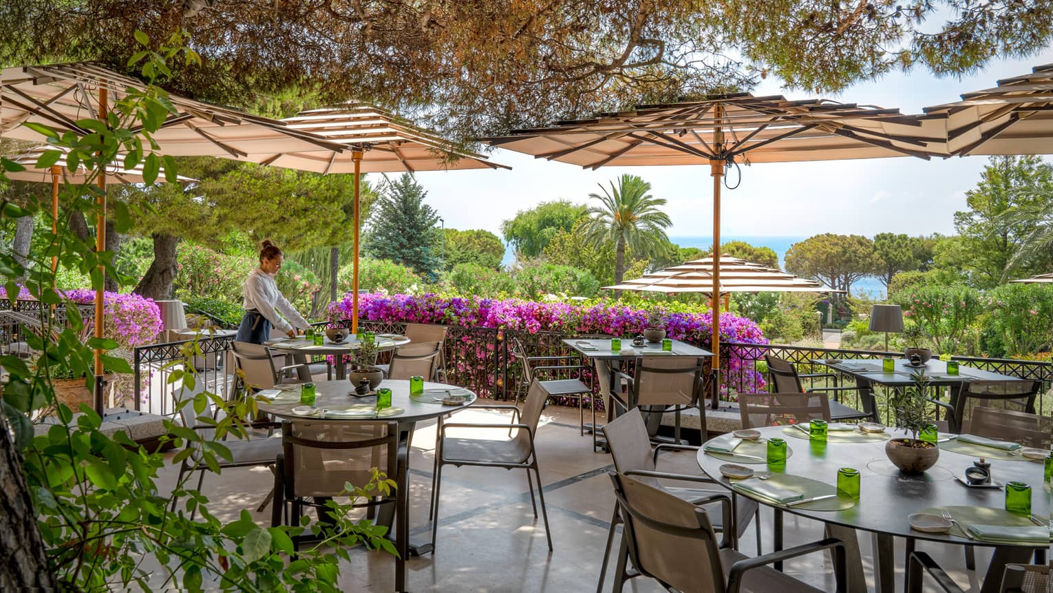 Waiter sets a table on outdoor restaurant terrace, surrounded by greenery and magenta-coloured flowers