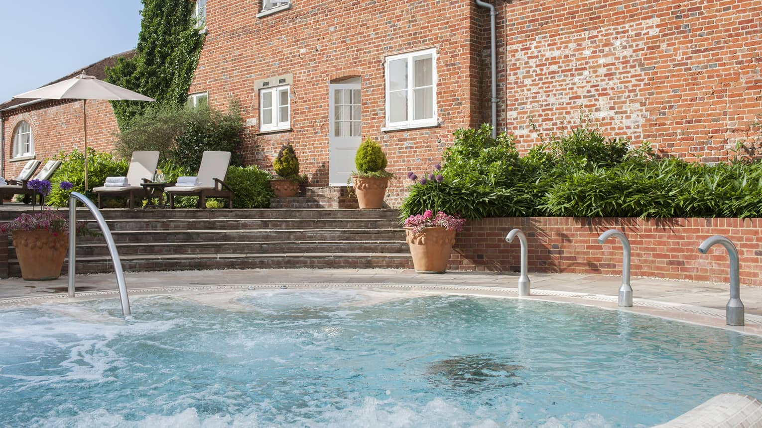 Outdoor swimming pool and steps under red brick hotel exterior on sunny day