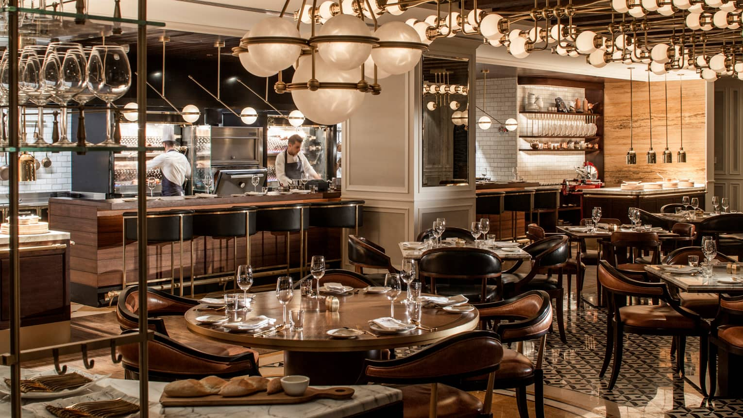 La Capitale dining room with dark, wood decor, round tables and chandeliers, globe chandeliers, chefs in open kitchen