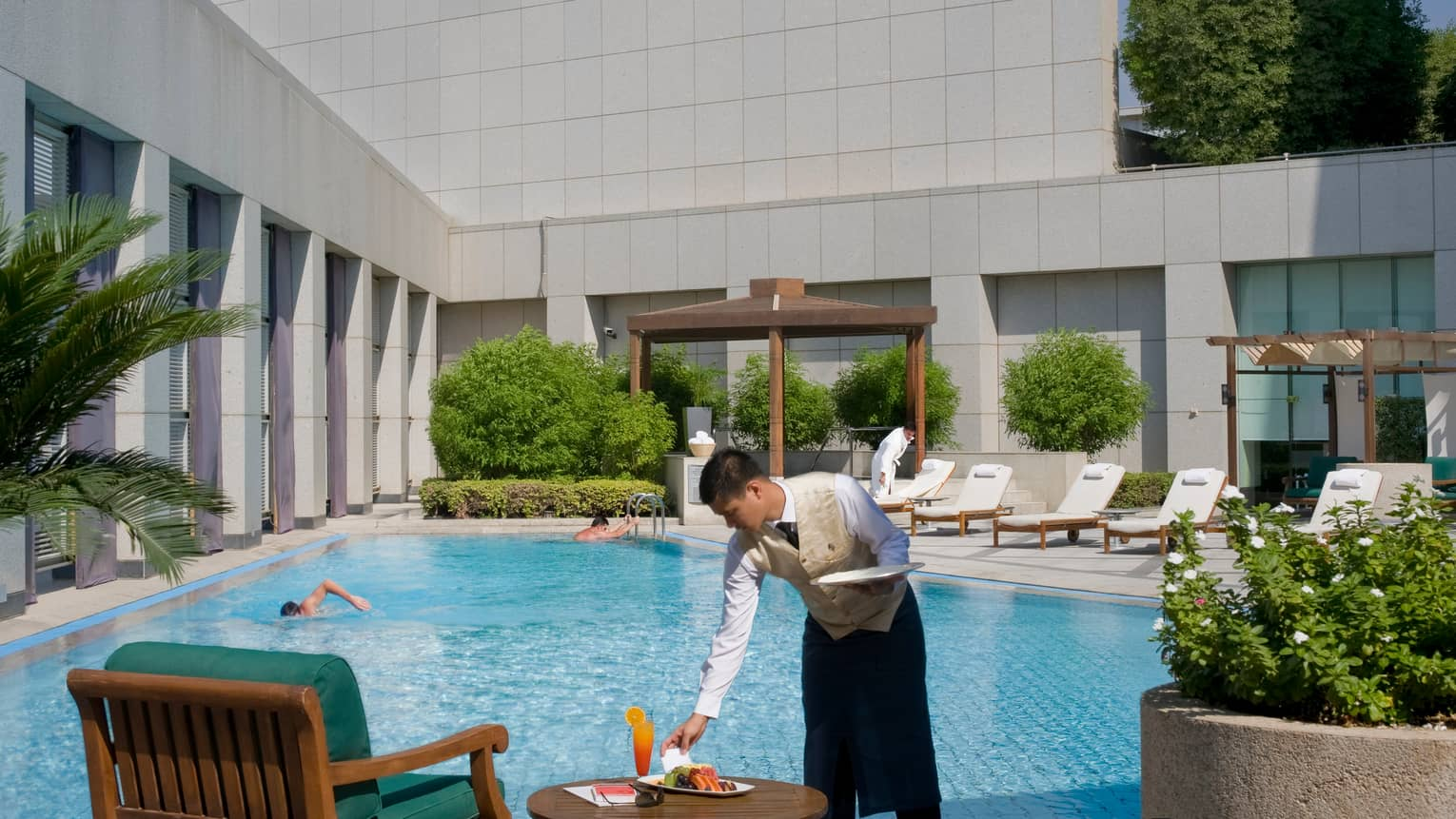 Server sets plate of fresh fruit next to cocktail on table beside sunny outdoor swimming pool where man swims laps