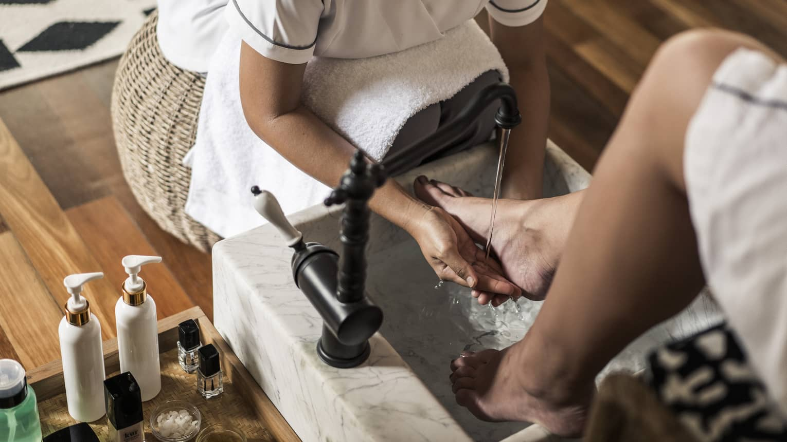 Spa staff sits on wicker stool, rinses woman's feet at pedicure station