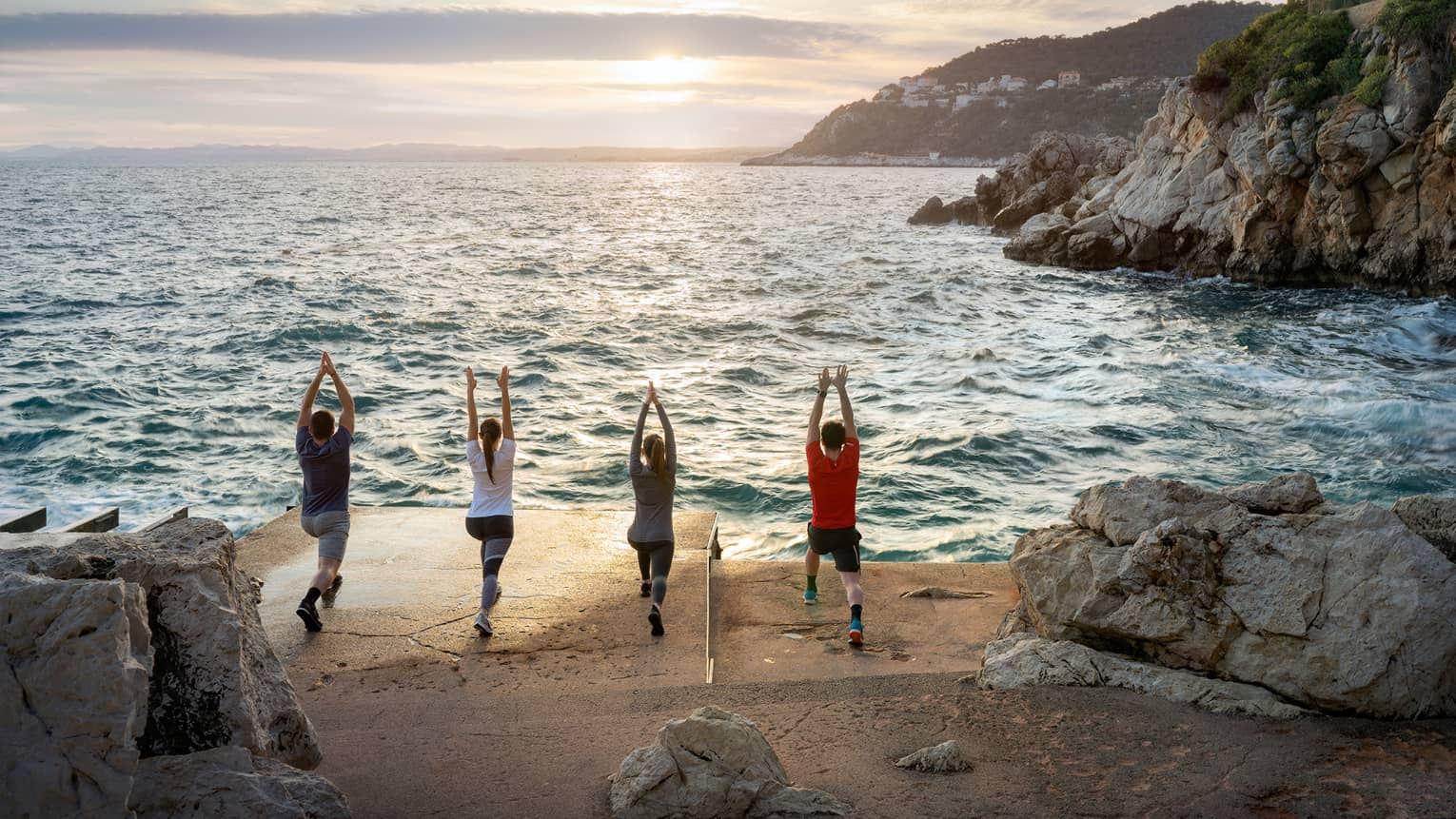 Rear view of four people doing yoga on sandy shore next to sea, rocky cliffs on right