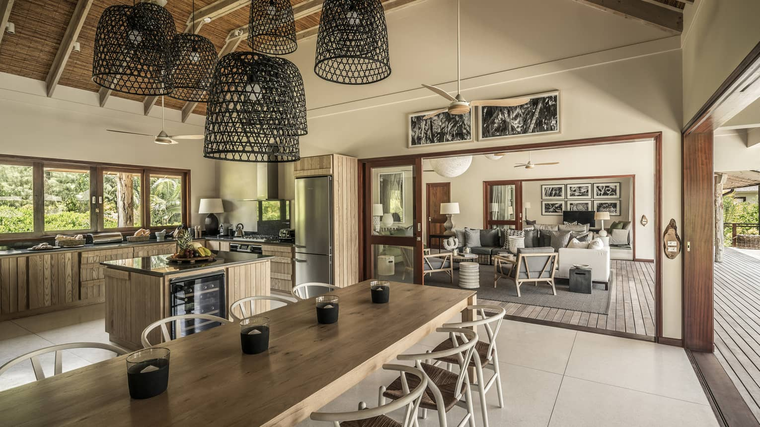Large basket-like chandeliers hang from gambrel roof over long wood dining table, large kitchen