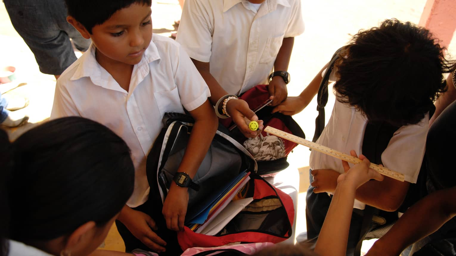 Young kids in white school uniforms sort through backpacks