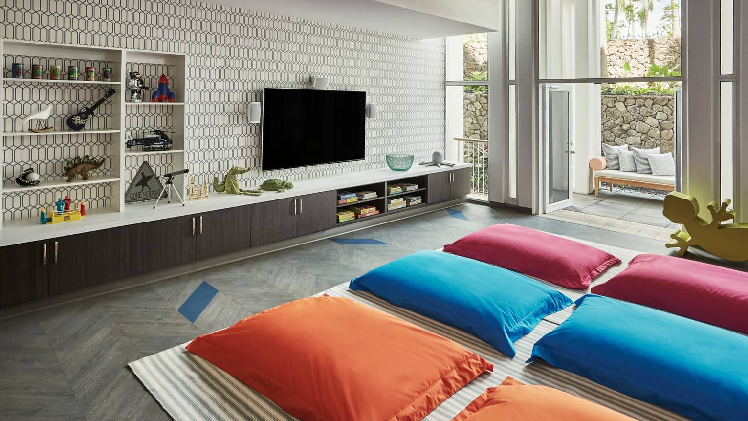 Camp Kohola media lounge with red, blue and orange pillows on floor facing TV