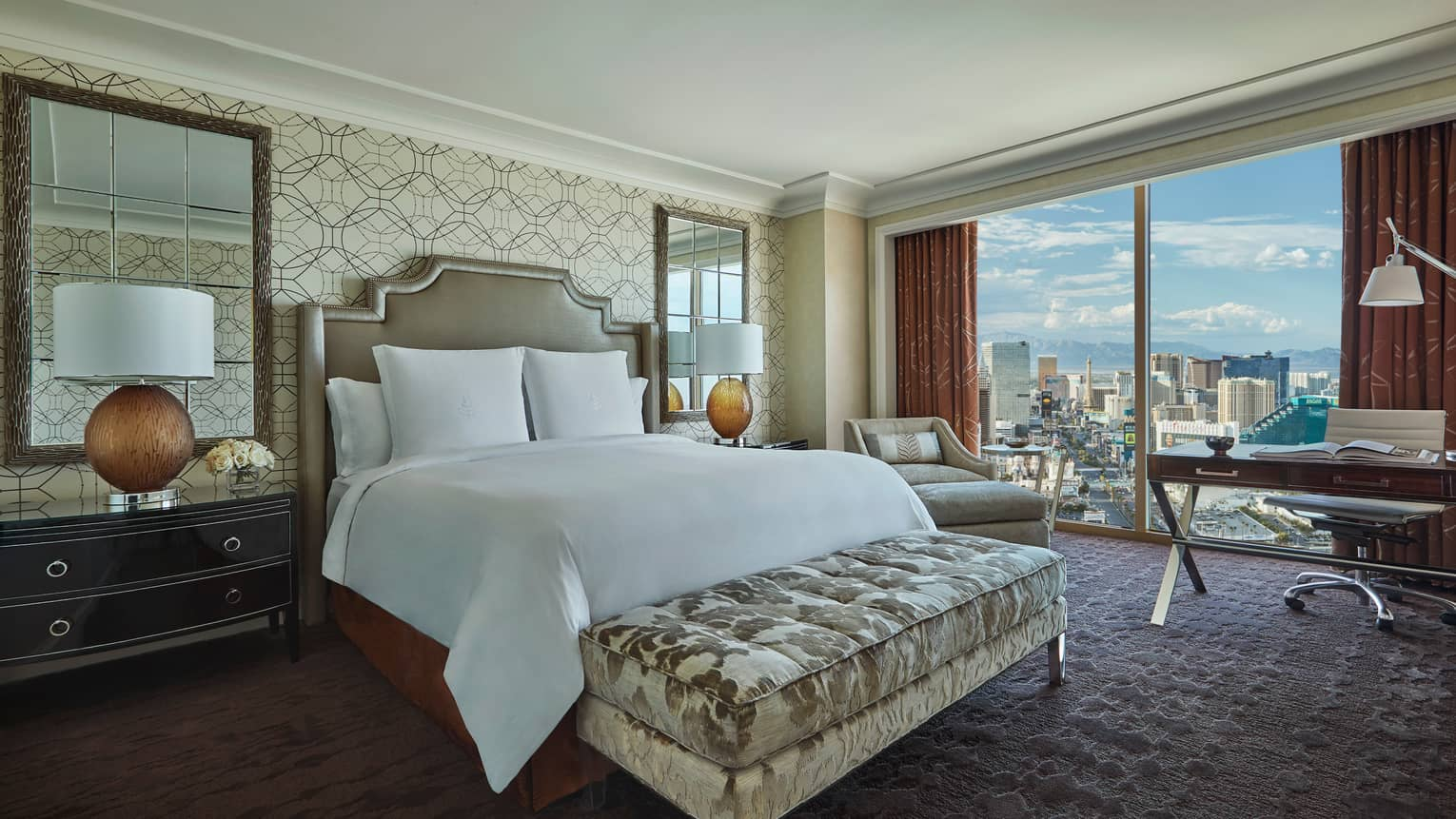 Strip-View room bed with plush velvet bench, mirrors, lamps by bed, desk by window