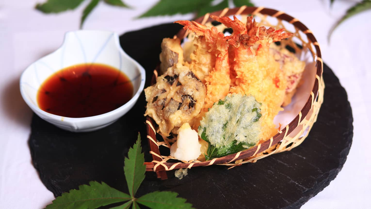 Fried prawn tempura in basket next to small bowl with sauce