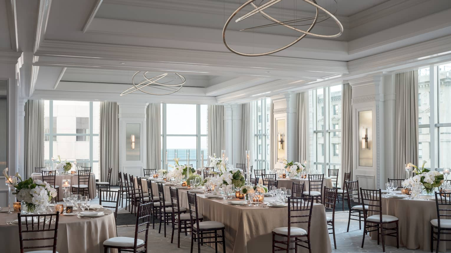 Ballroom with high ceilings and large windows, one long table surrounded by round tables
