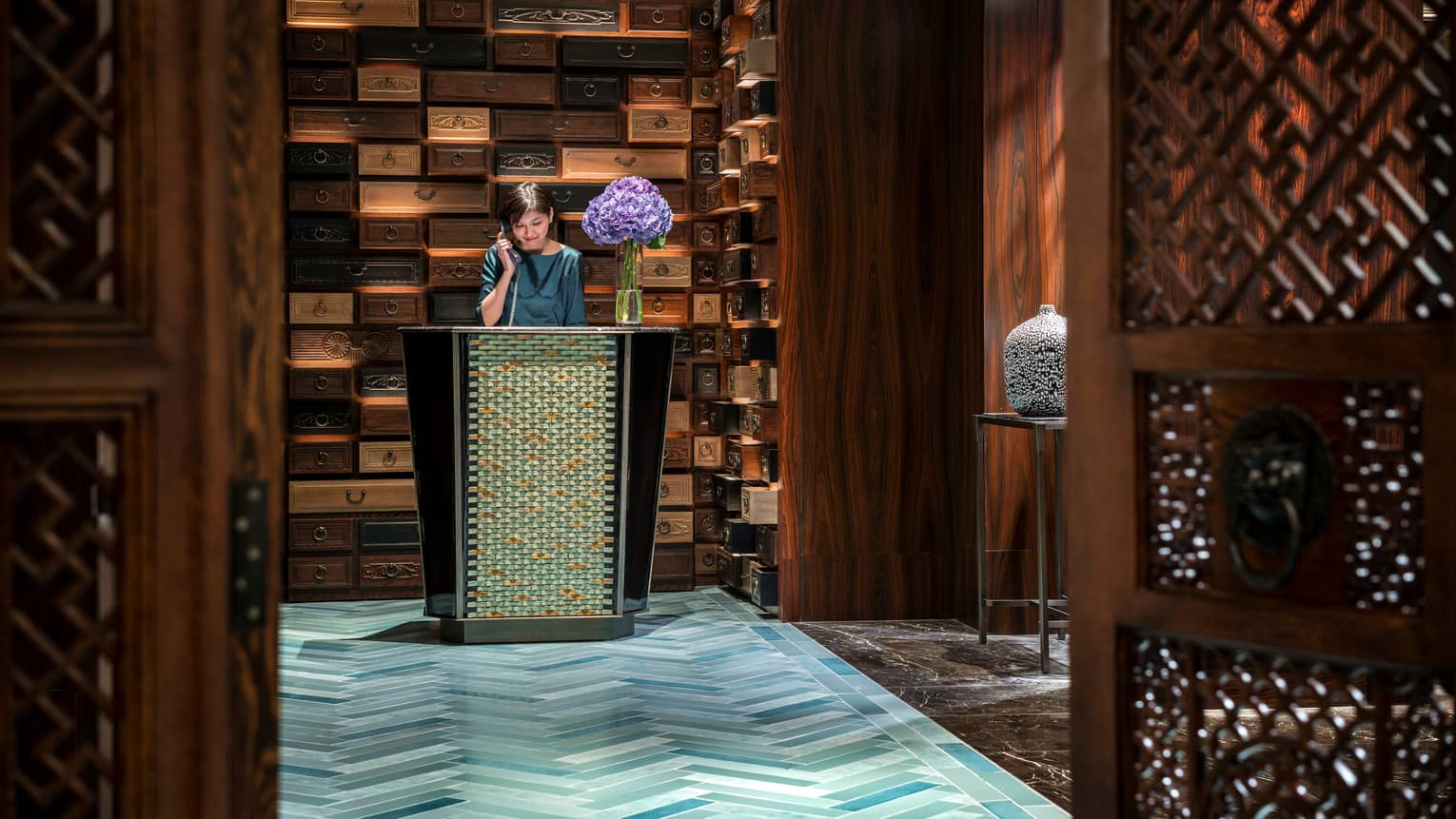 Hotel staff answers telephone at reception desk in front of decorative wall made from wood drawers