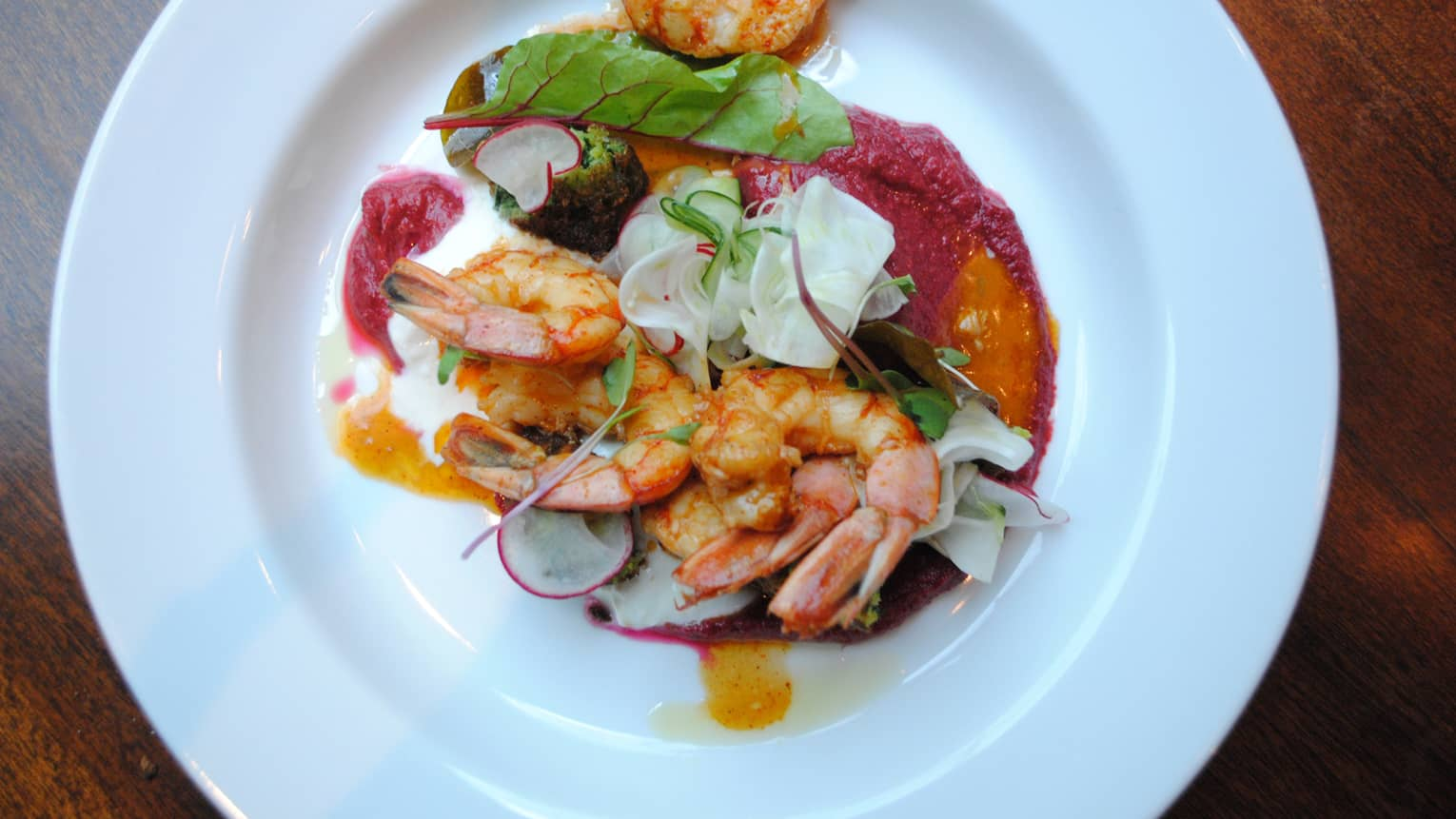 A shrimp dish is served with radishes, greens and a creamy sauce