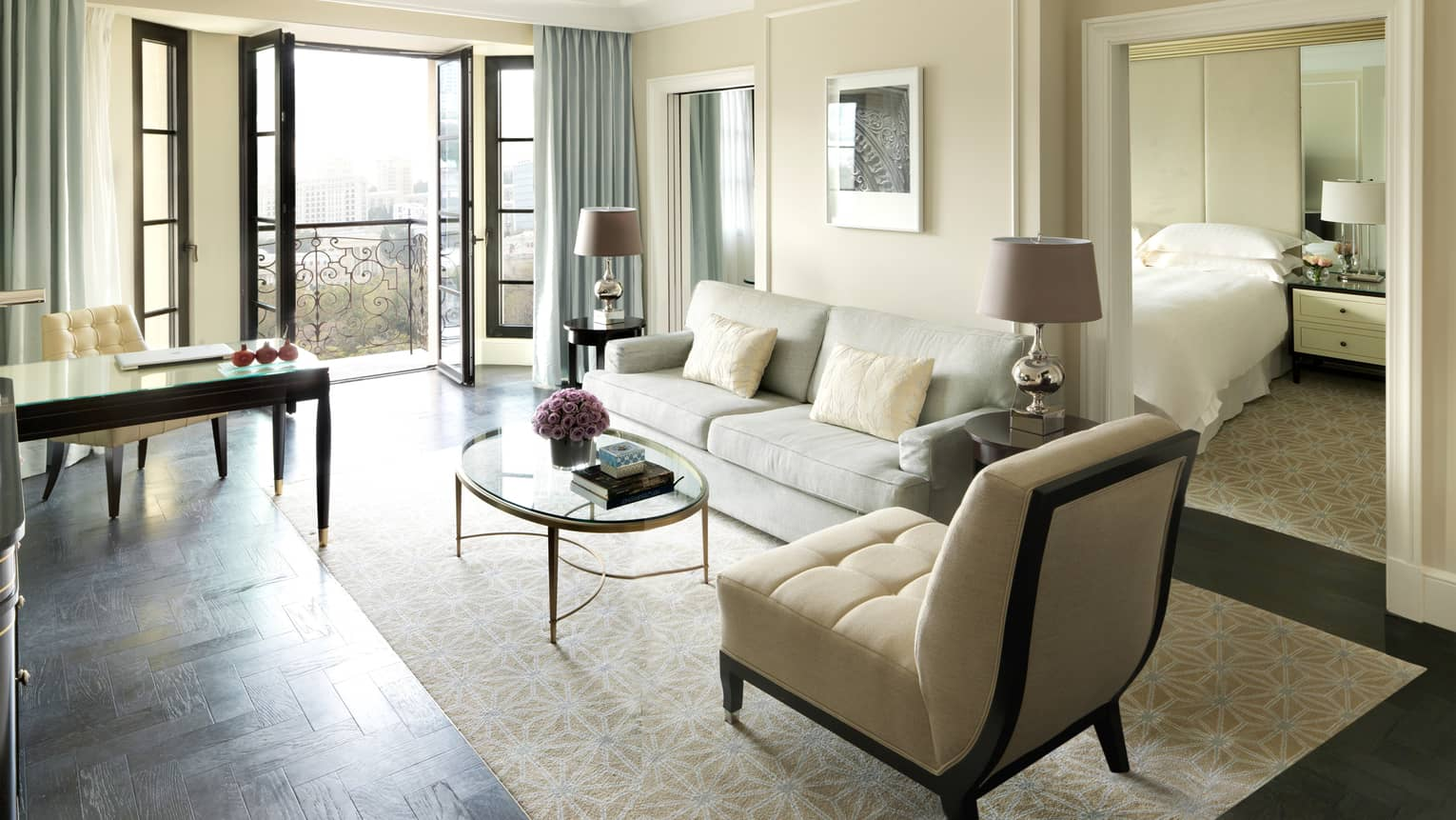 Executive Suite living room with open French doors, white sofa and plush chair, writing desk, door to bedroom