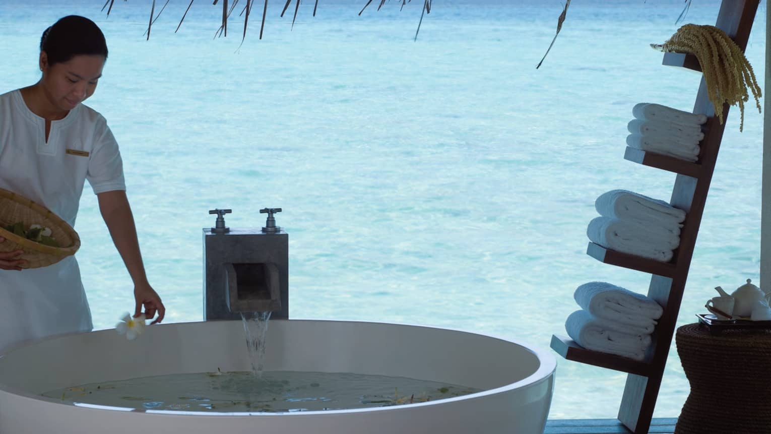 Spa & Ayurvedic Retreat staff places flowers in free standing tub on patio over lagoon