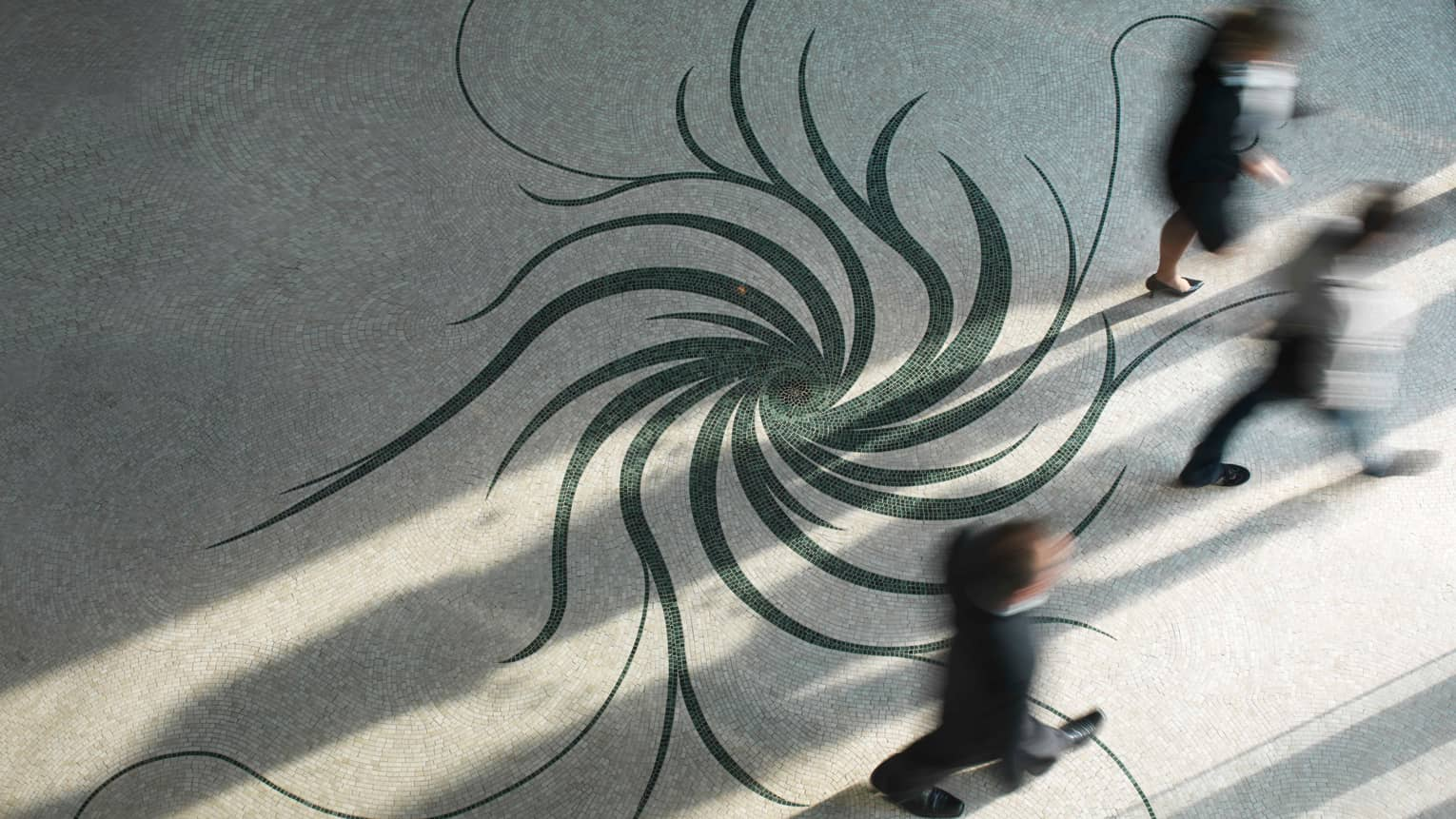 Aerial view of mosaic tiles in swirl patterns as people walk by