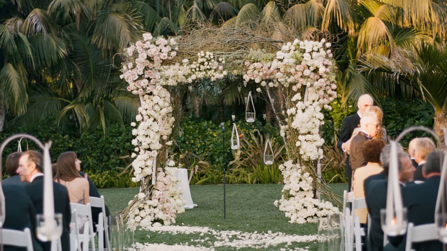 Wedding ceremony on lawn, guests in chairs facing flower-covered altar