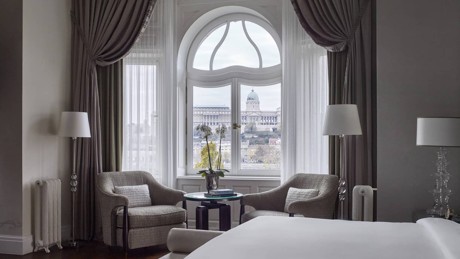 Buda Castle Presidential Suite is furnished with a two sitting chairs next to a curved window, lamps, a large bed and gray curtains.
