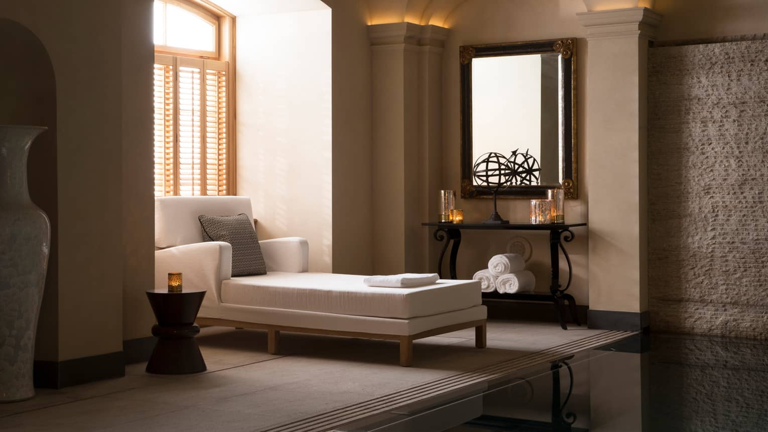 Long white chaise with accent pillow under sunny spa window with shutters, candles on shelves in room