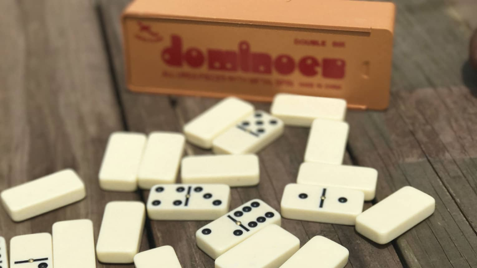 Dominoes on table, box in background