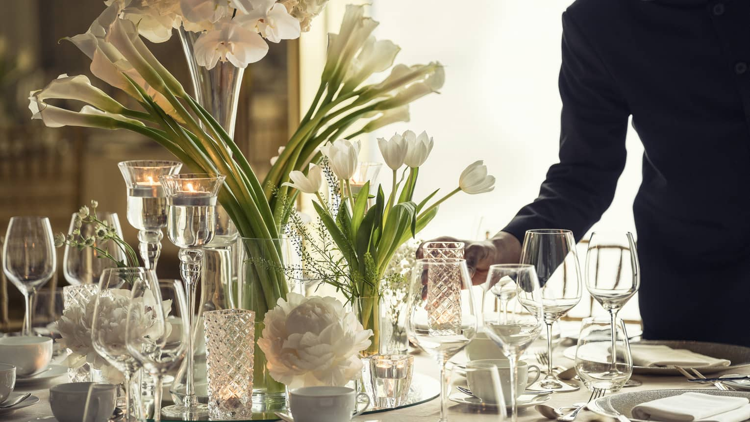 Hotel staff sets elegant banquet dining table with crystal glasses, vases with white flowers
