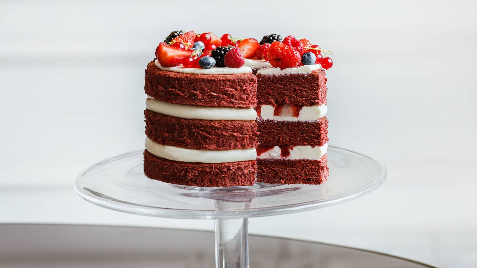 Red velvet layer cake topped with fresh berries on glass cake stand