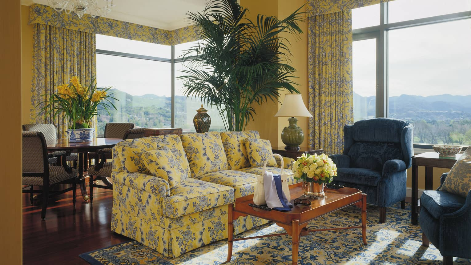One-bedroom suite blue and yellow floral sofa, armchair, coffee table with purse, sunglasses