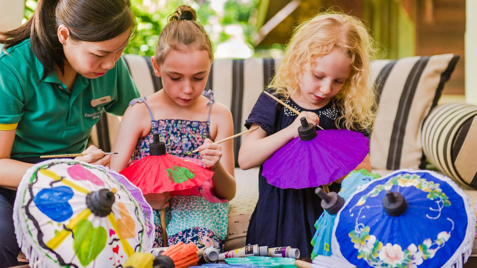 Kids Club staff helps young girls paint pictures on colourful paper umbrellas