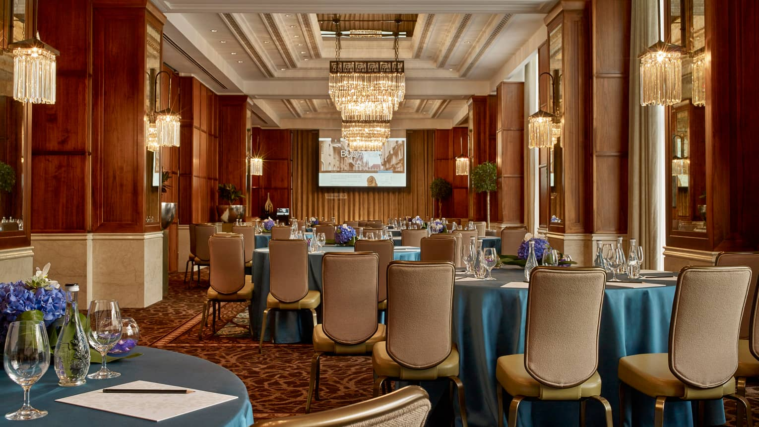 Gresham Room Art Nouveau-style ballroom tables with blue satin tablecloths, leather dining chairs, chandeliers