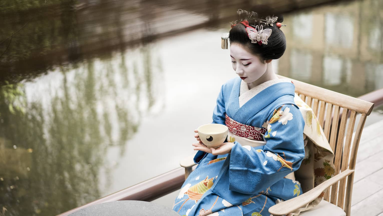 Geisha wearing traditional kimono robe, makeup sits on wood chair, holds tea cup