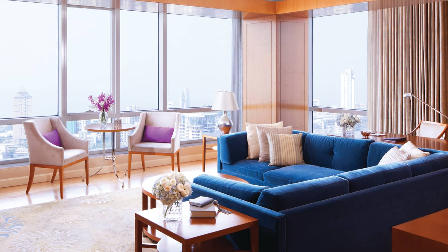 Deluxe Suite-Sea room with blue sectional sofa by floor-to-ceiling sunny windows, chairs