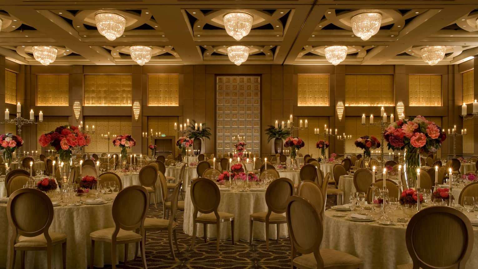 Dimly lit event room with chandeliers, tables set with large floral displays, glasses and candles