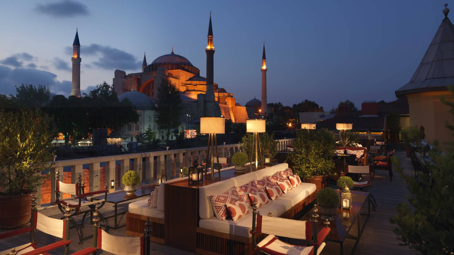 A'YA Rooftop Lounge benches, tables at night with mosque in background