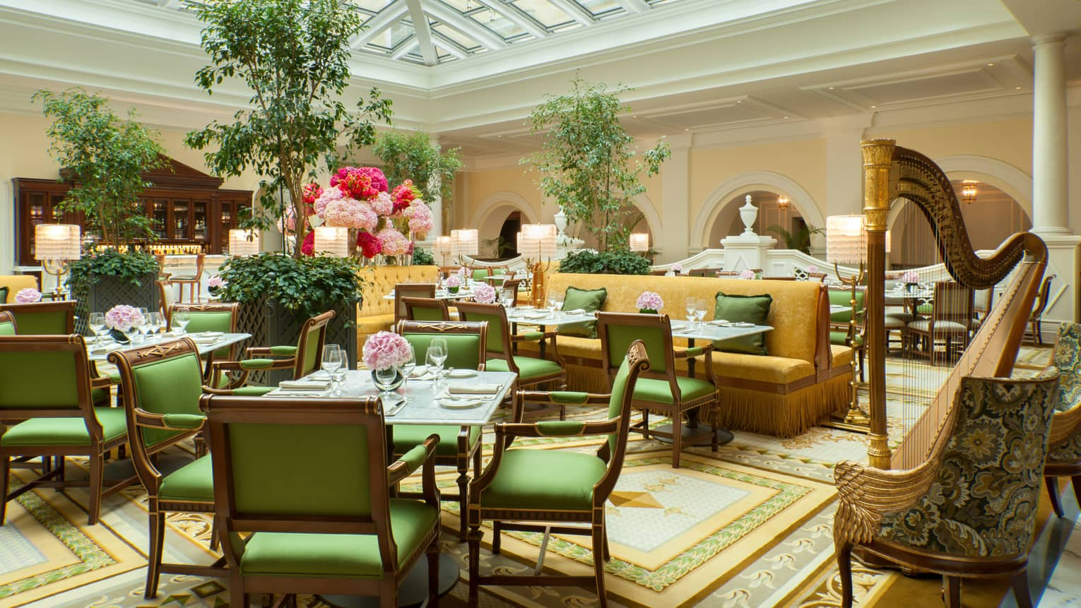 Tea Lounge dining tables with green chairs, gold accents, large harp under vaulted ceiling, skylight