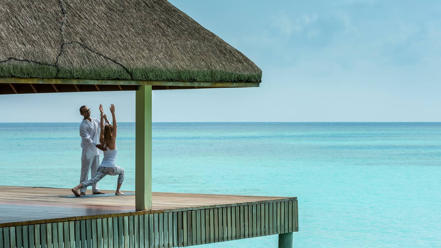 Yogi helps woman into yoga pose on thatched roof pavillion over blue ocean