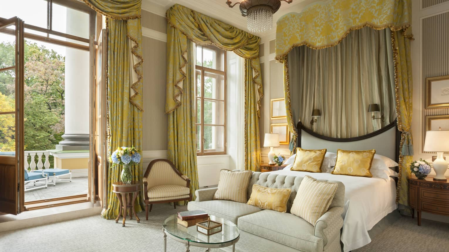 Presidential Suite master bedroom bed with loveseat at foot, gold curtains cascading from high ceilings