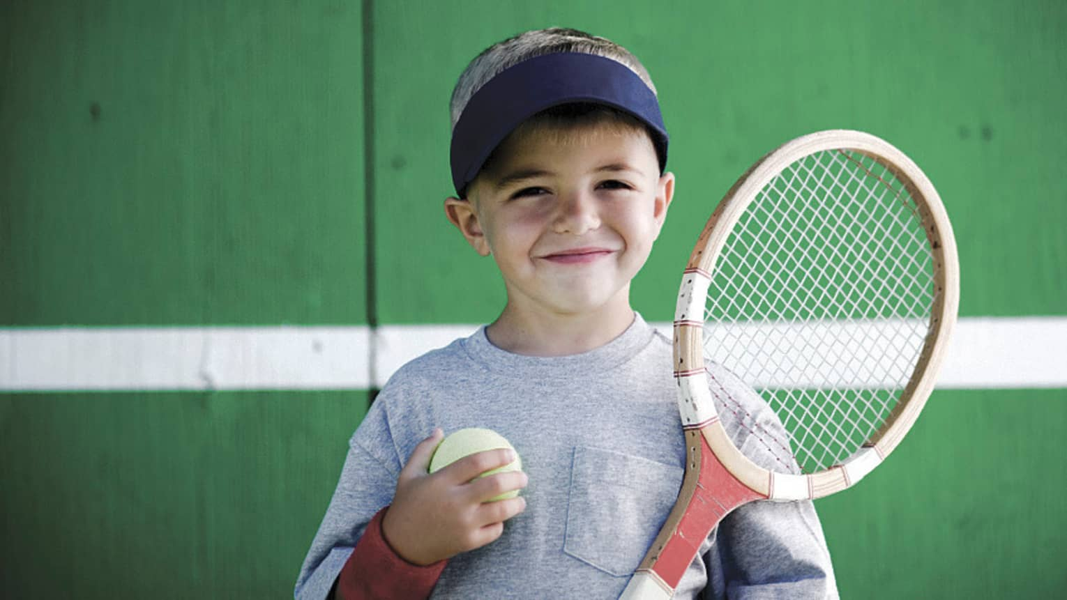 Smiling young boy holding tennis racket, ball