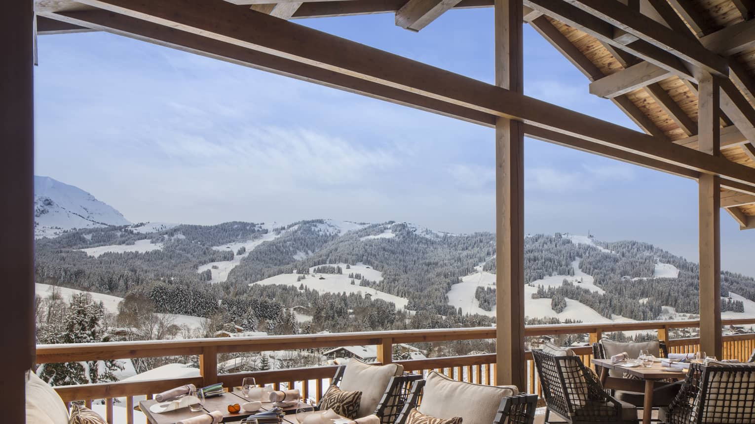 Dining tables, chairs, cushions under wood roof looking over snow-covered mountains