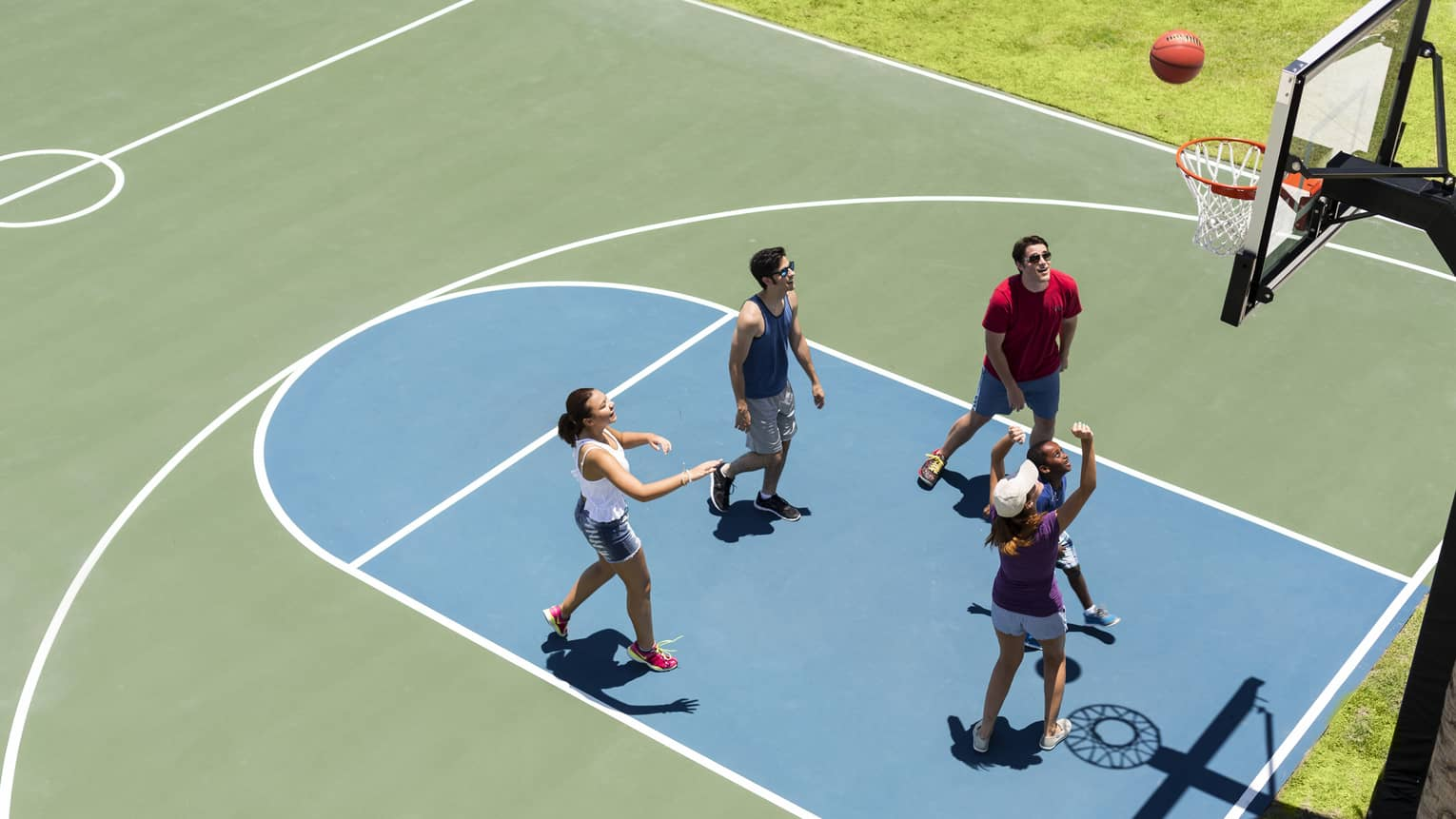 Aerial view of group of friends on basketball court, throwing ball in net
