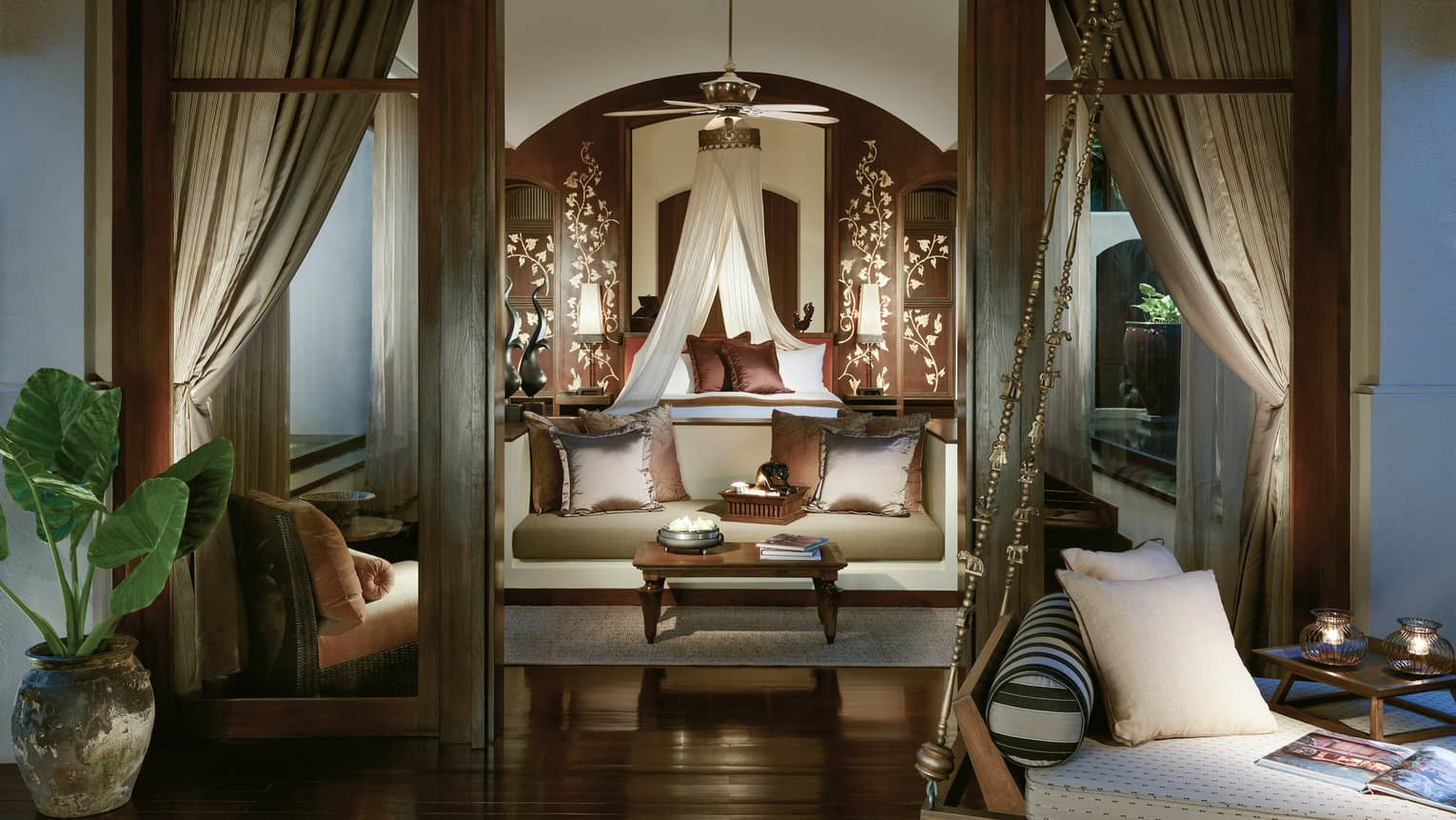 View from doorway into elegant Pool Villa with loveseat and brown silk pillows, white canopy over bed