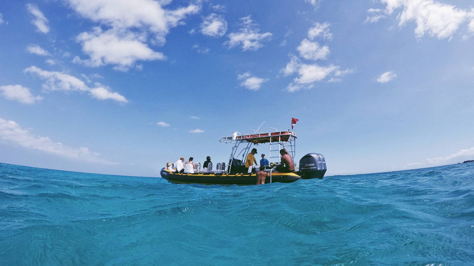 People sit on edge of small inflatable motor boat, prepare to snorkel