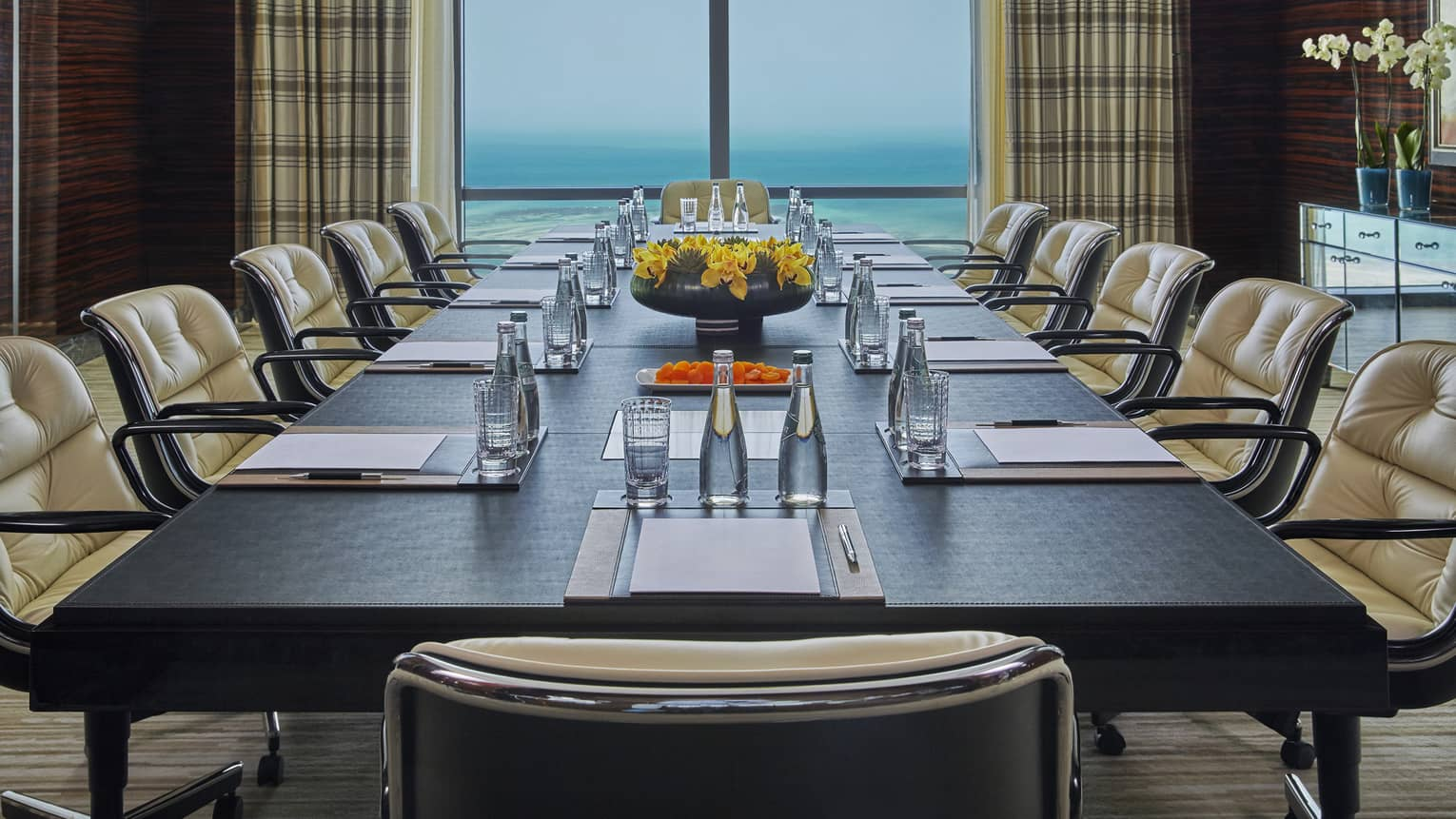 Large boardroom meeting table lined with plush leather chairs in front of window with ocean view
