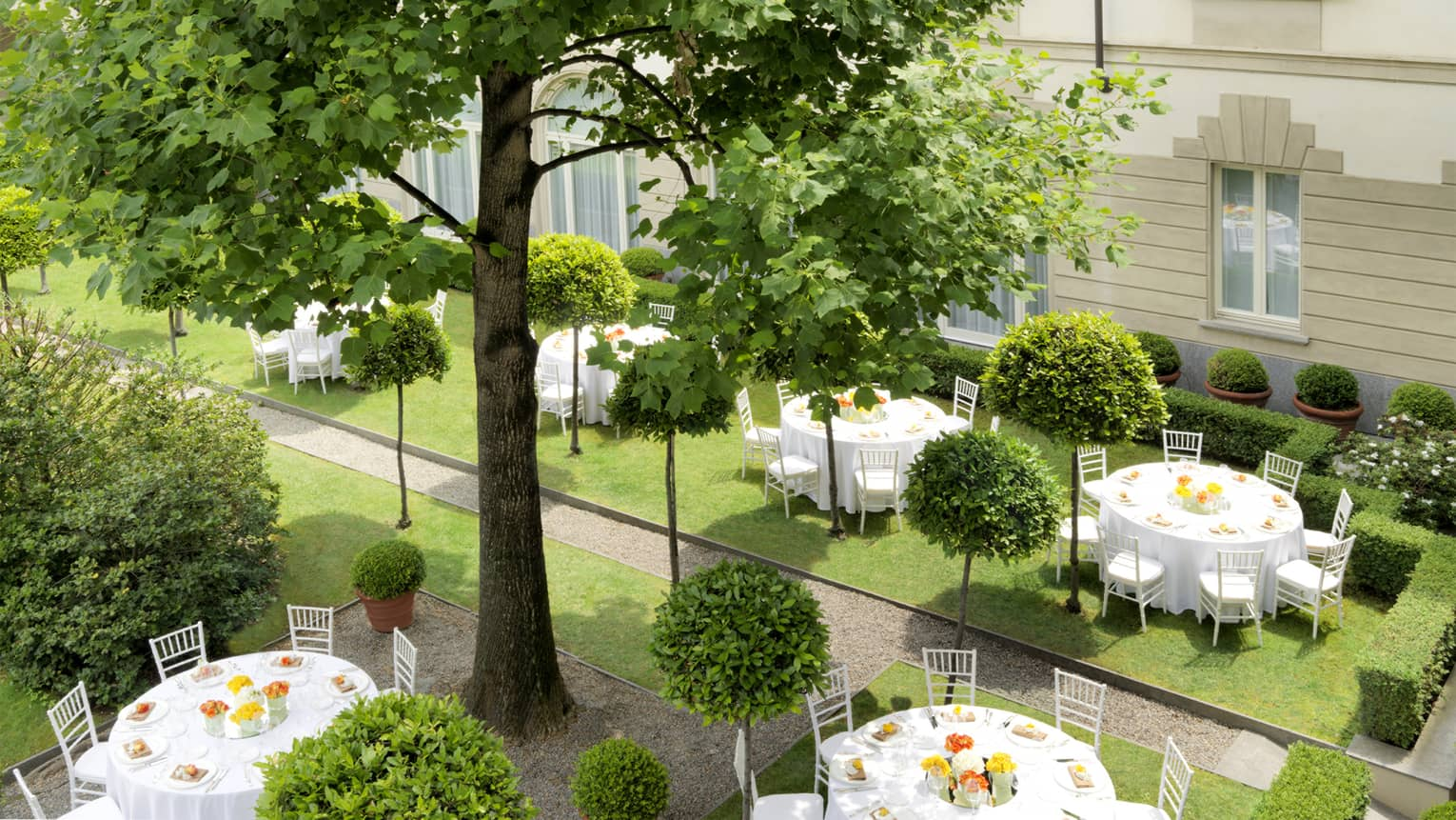 Round banquet tables with white linens on garden event lawn
